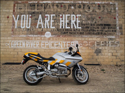 "Picture of an R1100S in front of a wall with the text: ""You are here"""